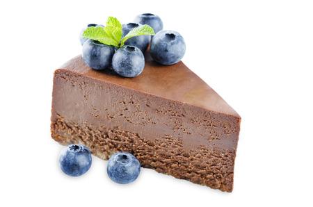 Schokoladenkäsekuchen mit frischen Beeren und Minzblättern isoliert. das Tonen. selektiver Fokus Standard-Bild