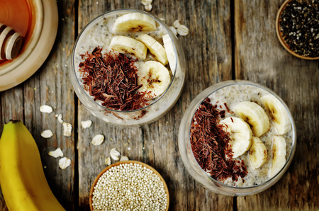 Durante la noche, plátano, avena, quinua, pudín de semillas de chía decorado con rodajas de plátano fresco y chocolate. viraje. enfoque selectivo
