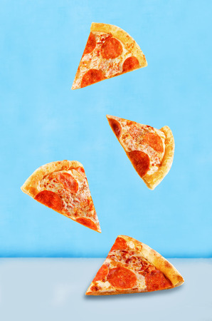 Pizza with pepperoni, tomato sauce and cheese on a blue background. toning. selective focus