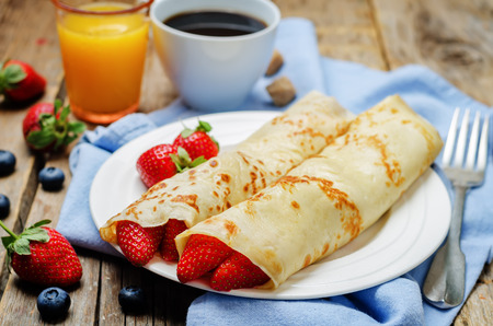 Crepes with strawberries on a wood background. toning. selective focus