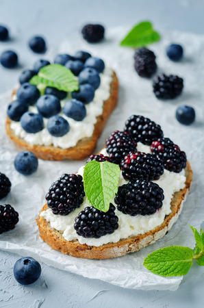 Blueberry and blackberry ricotta rye sandwiches. toning. selective focus