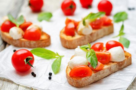 Caprese bruschetta with fresh tomatoes and Basil leaves. Stock Photo