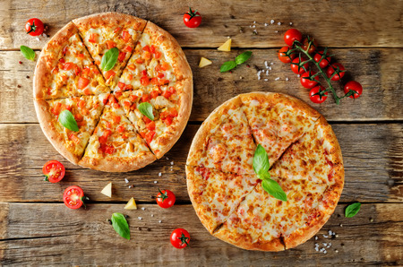 Pizza with cheese, chicken and fresh tomato slices on a wood background. toning. selective focus