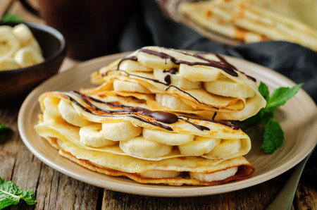 Crepes with fresh banana slaces and dark chocolate. toning. selective focus