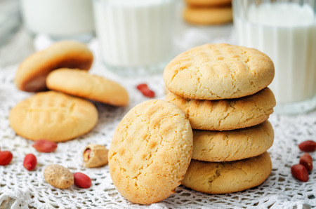 Peanut butter cookies with glasses of milk on a wood