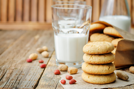 Biscuits au beurre d'arachide avec des verres de lait sur un bois
