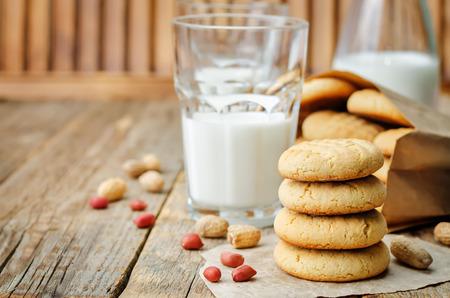 Galletas de mantequilla de maní con vasos de leche en una madera