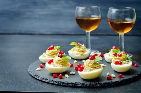 Blue cheese deviled eggs with pomegranate and fresh parsley leaves. toning. selective Focus