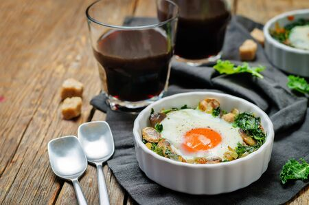 Kale mushrooms baked egg with cups of coffee on a wood