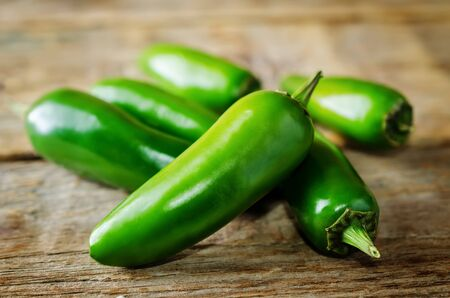 Fresh jalapeno peppers on a dark wood background. toning. selective focus