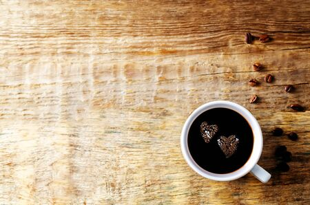 Cup of hot black coffee with coffee beans on dark wood background. Selective focus