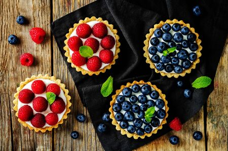 Raspberry and blueberry tartlets with fresh berries and mint leaves. Selective focus