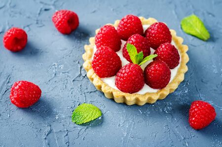 Raspberry tartlets with fresh berries and mint leaves. Selective focus