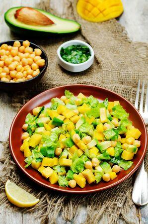 Mango avocado chickpeas salad on a wood background. Selective focus