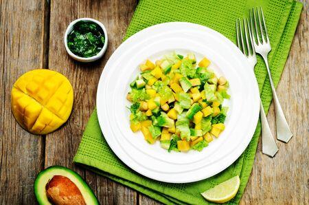 Mango avocado chickpeas salad on a wood background. Selective focus Standard-Bild - 126727643
