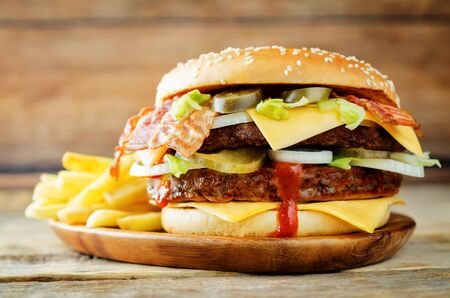 Meat Burger with salad, cheese, tomato and ketchup sauce on a wood background.