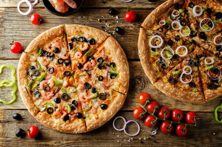 Pizza with shrimp, olives, green pepper and onion on a wood background. toning. selective focus