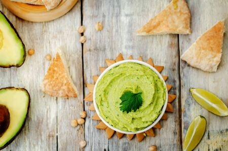 avocado hummus with pita and fresh avocado slices on a wood background. toning. selective focus
