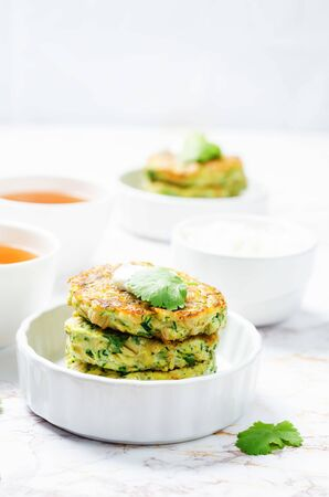 Zucchini ricotta cilantro fritters with fresh cilantro leaves. toning. selective focus