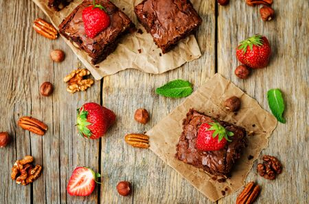 Chocolate nut brownie cake decorated with strawberries. selective focus