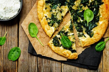 Spinach Ricotta Galette with fresh spinach leaves on a wood
