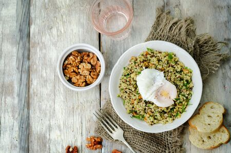 Basil nuts pesto quinoa with walnuts, parsley and poached egg. toning. selective focus Imagens