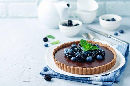 Tarta czekoladowa z jeżynami i jagodami. tonowanie. selektywne skupienie