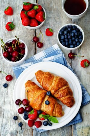 Croissants with fresh berries and mint leaves on a wood background. toning. selective focus