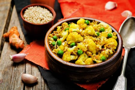 cauliflower green peas turmeric rice on a wood background. toning. selective focus Imagens