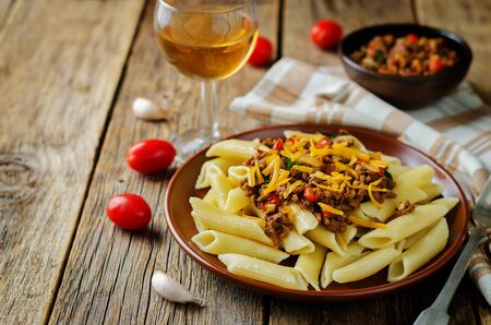 Minced beef pepper pasta with glass of wine. toning. selective focus Standard-Bild