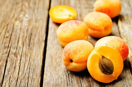 Apricots with slices on a wooden