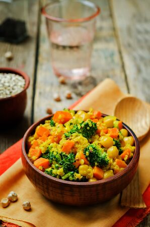 Quinoa broccoli carrot curry on a wood background. toning. selective focus Фото со стока