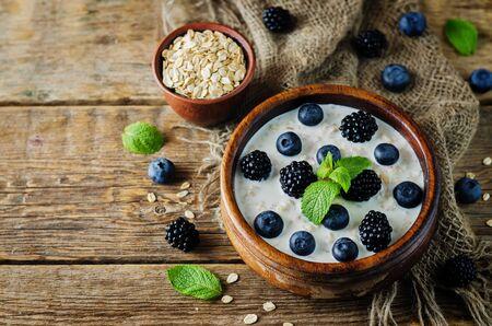 Oatmeal porridge with fresh blueberries and blackberries. toning. selective focus Archivio Fotografico