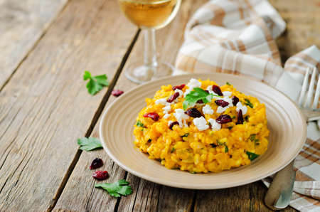 Pumpkin risotto with dried cranberries and goat cheese. toning. selective focus 版權商用圖片