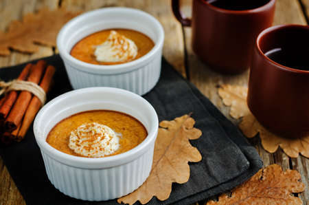 Baked Pumpkin pudding with whipped cream and cinnamon. toning. selective focus