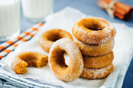 Baked pumpkin donuts with glasses of milk. toning. selective focus