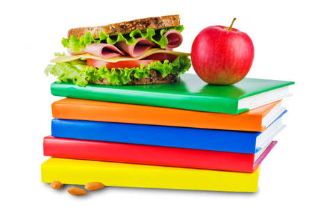 school lunch with a sandwich, fresh fruits and multicolored books on a white isolated background. toning. selective focus 版權商用圖片