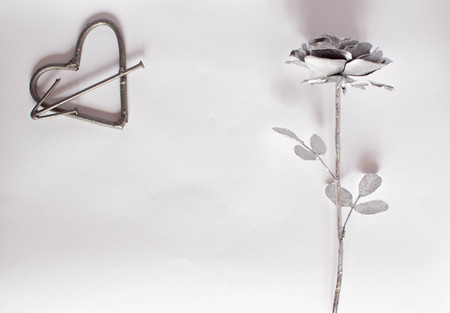 Forged heart handmade metal nails on a white background. Forged rose and heart. Flat lay, top view minimal concept.