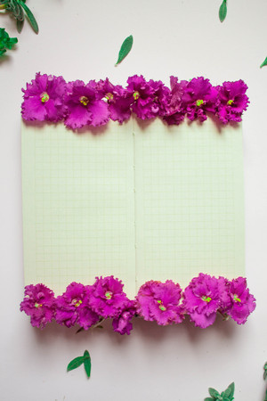 Empty notebook decorated purple flowers on a white background, top view. Notepad decorated with green leaves and violet. Flat lay