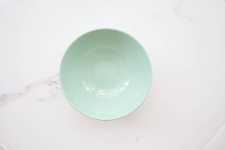 plate on white marble. green ceramic bowl on a white marble background. top view.