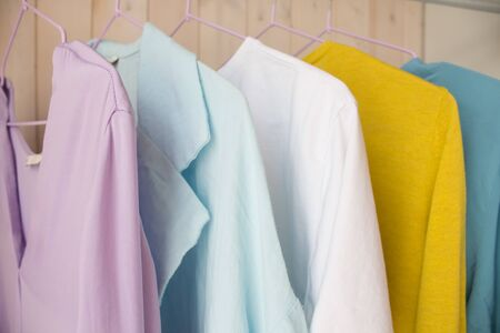spring-summer wardrobe. multi-colored clothes on a hanger in a closet. quarantine, leisure activities