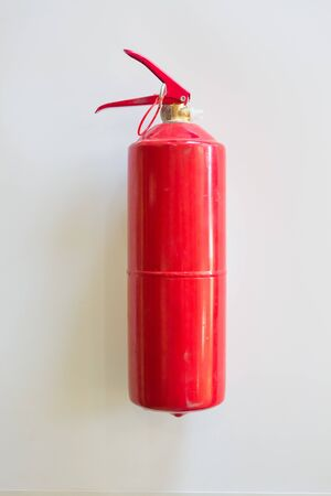 fire extinguisher on a white wall background. fire concept.