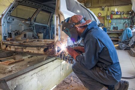 auto welder in the process of welding a car body in a workshop. auto repair concept Banque d'images