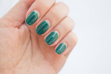 Damaged female nail with green manicure. Peeled off gel polish with nails. Home manicure concept.