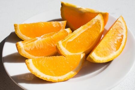 slices of ripe orange closeup with drops of juice on a white background.