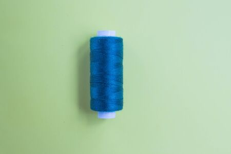 Blue indigo threads on a green background close-up. Needlework and hobby concept. Top view. Flat lay composition