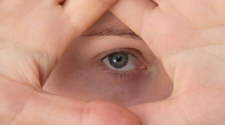 A young woman shows a symbol of the Illuminati, an eye in a triangle. Pyramid of Masons and Illuminati