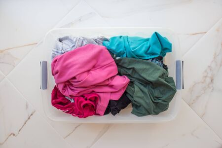 Rectangular basket with dirty linen on a white marble floor close-up, top view. Bright underwear of different colors.
