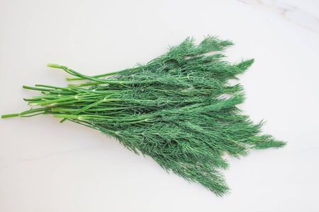 A bunch of fresh dill with a vegetable garden on the table. green food for raw food, a mix of vitamins for health.