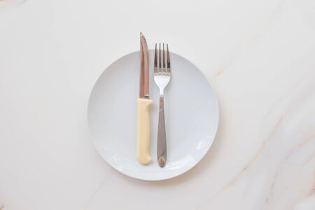 Empty white plate with cutlery on a marble table, saucer, fork and knife. The concept of diet, fasting.